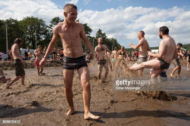 Festival goers play in a pool of muddy water at the 2017 Woodstock Festival Poland on August 4 2017 in Kostrzyn Poland The threeday rock music...