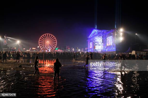 Festival goers play in the water as others watch a rock concert in the backgroud at the 2017 Woodstock Festival Poland on August 4 2017 in Kostrzyn...