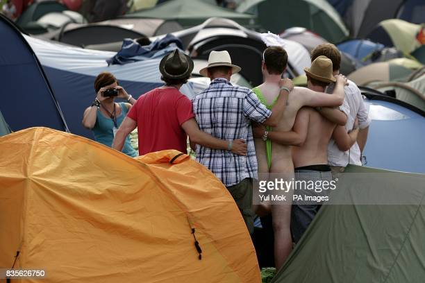 A festival goers pose for pictures with a man wearing a mankini during the 2009 Glastonbury Festival at Worthy Farm in Pilton Somerset