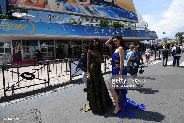 Festival goers pose in front of the festival's palace on May 8 2018 ahead of the opening of the 71st edition of the Cannes Film Festival in Cannes...
