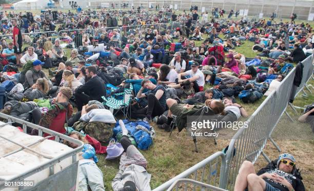 Festival goers queue for buses as they leave the Glastonbury Festival site at Worthy Farm in Pilton on June 26 2017 near Glastonbury England...