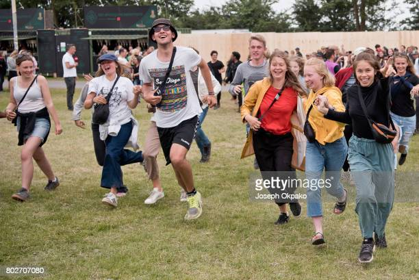 Festival goers rush rush into the main arena space on Day 5 of Roskilde Festival on June 26 2017 in Roskilde Denmark