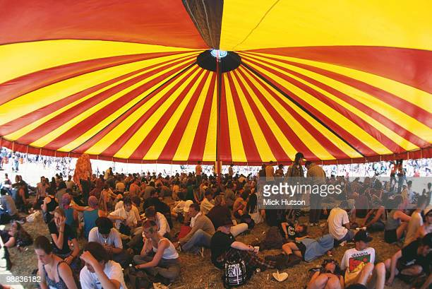 Festival goers sheltering from the sun under a marquee at Glastonbury Festival in June 1995