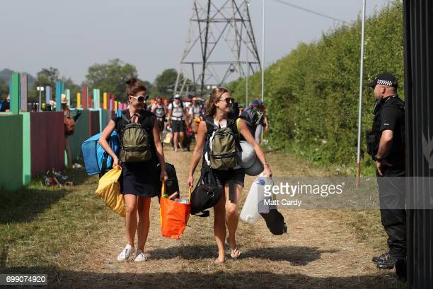 Festival goers smile at a police officer as the gates open at the Glastonbury Festival amid heightened security at Worthy Farm in Pilton on June 21...