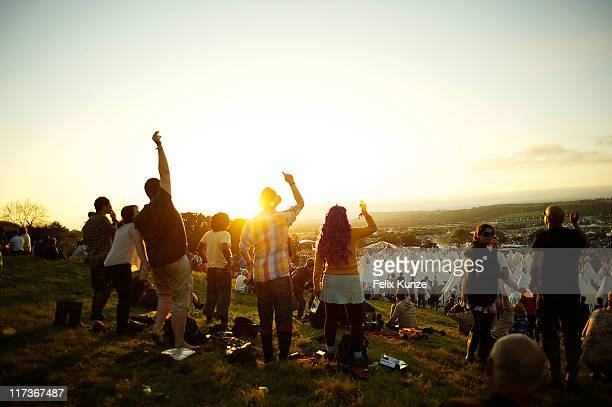 Festival goers soak up the sunset atmosphere during the third day of Glastonbury Festival 2011 at Worthy Farm on June 25 2011 in Glastonbury United...