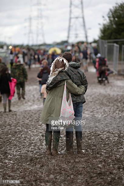 Festival goers stand in the mud as people arrive for the Glastonbury Festival, at Worthy Farm on June 22, 2011 in Glastonbury, England.