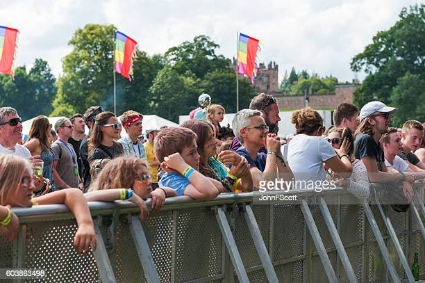 Festival goers standing behind the barrier at a music festival