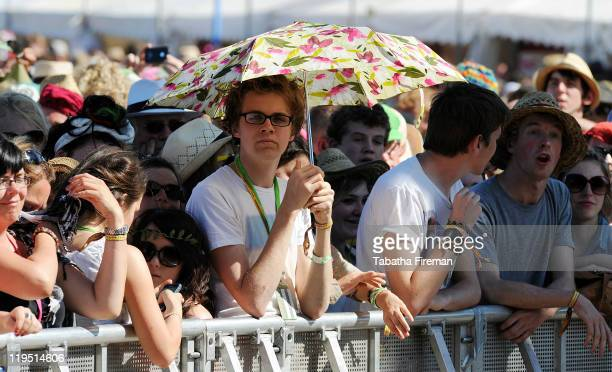 Festival goers take shade from the hot sunshine under umbrellas whilst watching Laura Marling perform on the Pyramid stage on the afternoon of the...