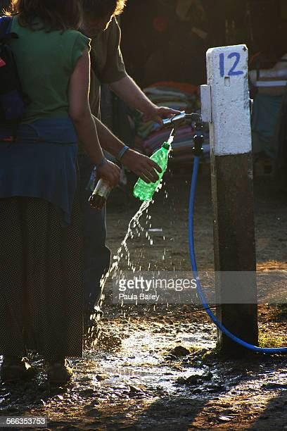 Festival goers topping up water bottles at a water point in the sunshine