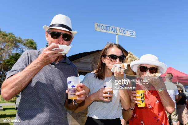 Festival goers try sheep testicles sold as mountain oysters during the Hokitika Wildfoods Festival on March 10 2018 in Hokitika New Zealand