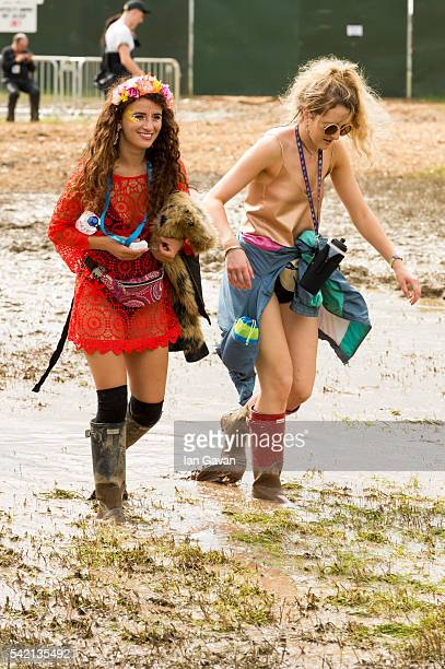 Festival goers wade though the mud at the Glastonbury Festival at Worthy Farm Pilton on June 22 2016 in Glastonbury England Now its 46th year the...