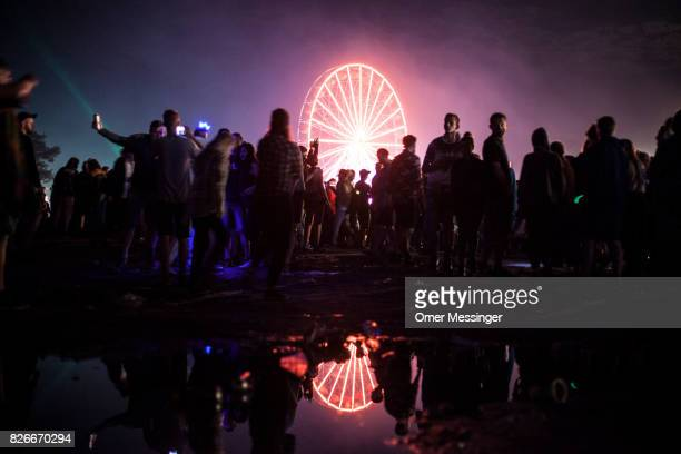 Festival goers walk at night time next to a water puddle as a lit Ferris wheel is seen in the background at the 2017 Woodstock Festival Poland on...