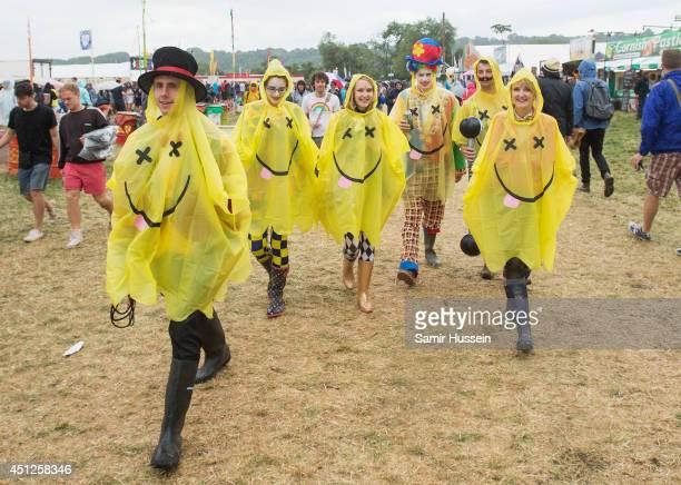 Festival goers walk in the rain at the Glastonbury Festival at Worthy Farm on June 26 2014 in Glastonbury England