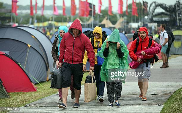 Festival goers walk in the rain at the Glastonbury Festival of Contemporary Performing Arts site at Worthy Farm Pilton on June 27 2013 near...