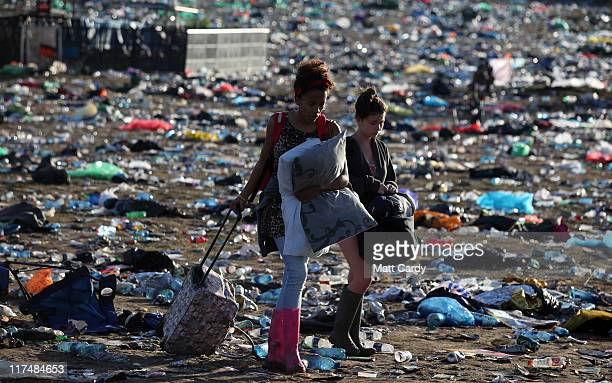 Festival goers walk through rubbish left in the main arena in front of the Pyramid Stage as they begin to leave the Glastonbury Festival site on June...