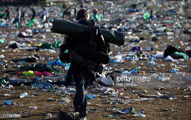 Festival goers walk through rubbish left in the main arena in front of the Pyramid Stage as they begin to leave the Glastonbury Festival site at...