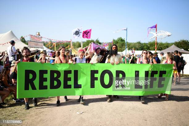 Festival goers walk through the festival site carrying a banner that says Rebel For Life as they take part in an Extinction Rebellion protest during...