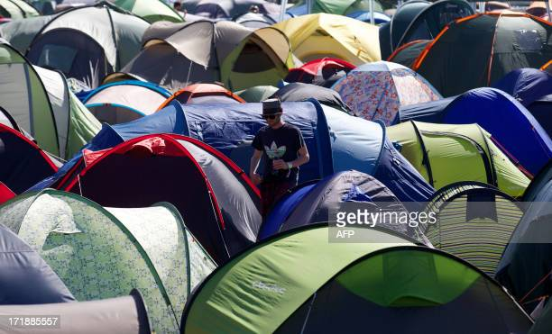 A Festival goers walks amongst tents on the fourth day of the Glastonbury Festival of Contemporary Performing Arts near Glastonbury southwest England...