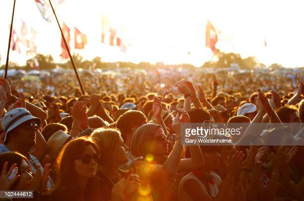 Festival Goers watch a band whilst the sun sets on the third day of Glastonbury Festival at Worthy Farm on June 26, 2010 in Glastonbury, England.