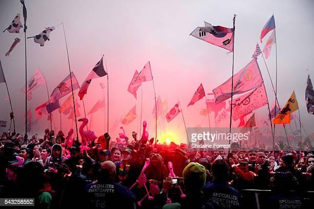 Festival goers wave flares at Glastonbury Festival 2016 at Worthy Farm Pilton on June 25 2016 in Glastonbury England