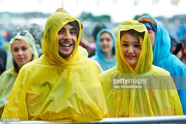 Festival goers wear matching yelow ponchos to protect themselves from the weather at the Glastonbury Festival at Worthy Farm on June 28, 2014 in...