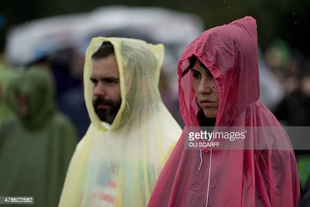 Festival goers wear raincoats as they watch Alabama Shakes perform on the Pyramid Stage on the first official date of the Glastonbury Festival of...