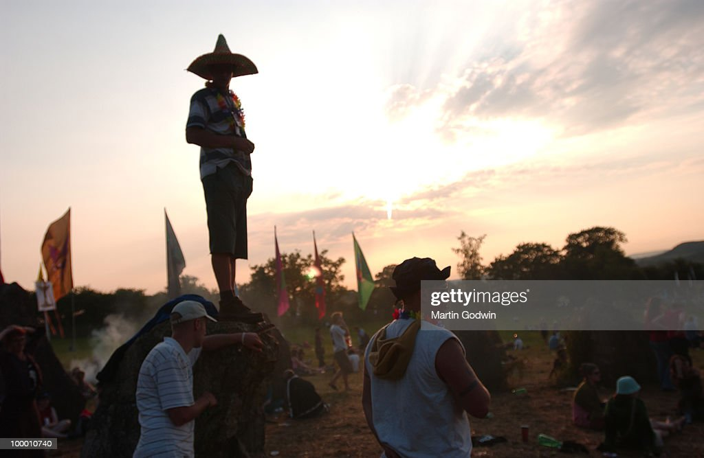 Festival goers with sombrero at the Stone Circle at dusk at Glastonbury, 23rd June 2005.
