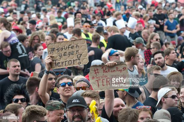 A festival guest holds up an antiterror sign as they enjoy the atmosphere in front of the Volcano Stage during the second day of 'Rock am Ring' on...