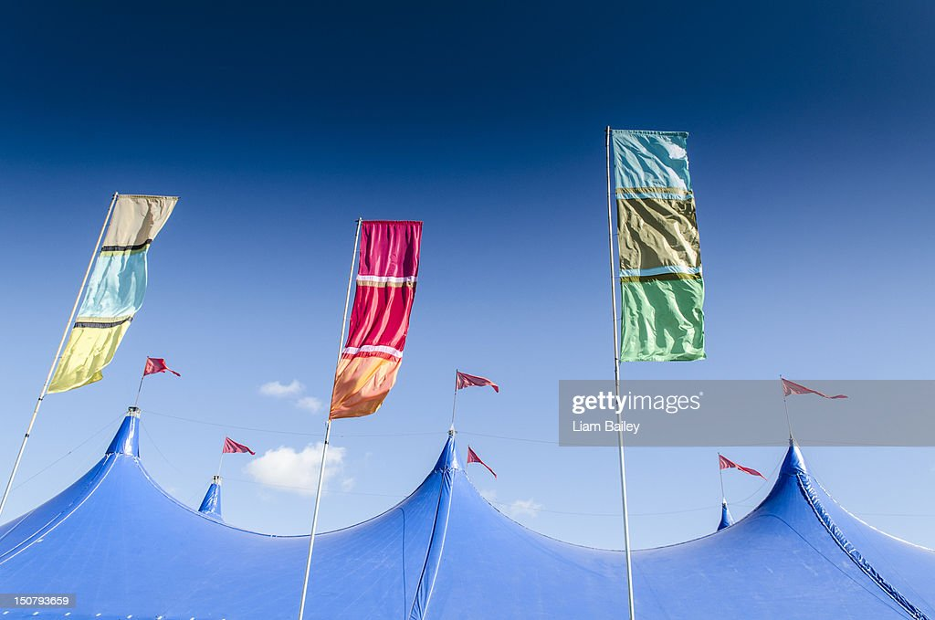 Festival tent top and coloured flags : Stock Photo