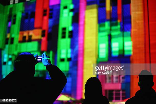 Festival visitors watch the 'Mechanised Colour Assemblage' installation illuminated on the Museum of Contemporary Art Australia façade as part of the...