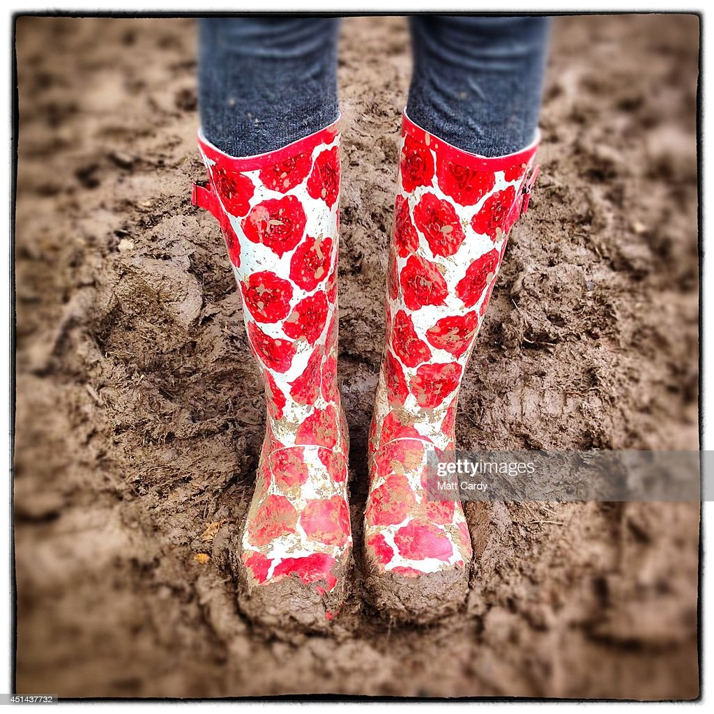 Festival-goer Carley Ashton poses in the mud with her wellies bought from Millets for £35 at the Glastonbury Festival site on June 29, 2014 in Glastonbury, England. Gates opened on Wednesday at the Somerset dairy farm that plays host to one of the largest music festivals in the world. Tickets to the event, which is now in its 44th year, sold out in minutes even before any of the headline acts had been confirmed. The festival, which started in 1970 when several hundred hippies paid £1, now attracts more than 175,000 people