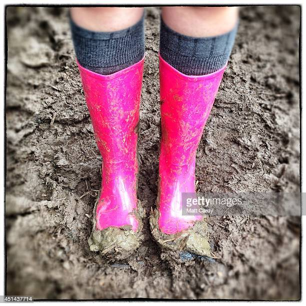 Festivalgoer Charlotte Mollert poses in the mud with her wellies bought online for £15 at the Glastonbury Festival site on June 29 2014 in...