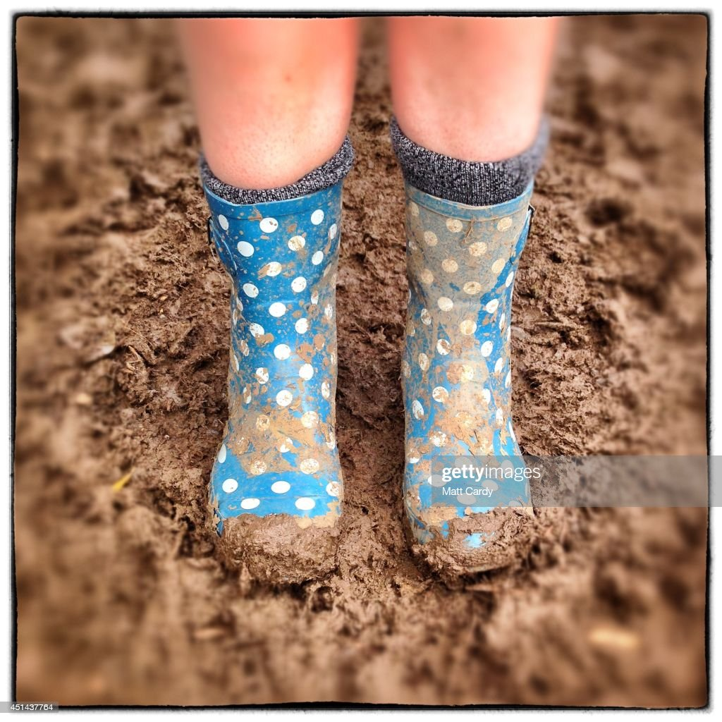 Festival-goer Eleanor Ashton poses in the mud with her wellies bought from Asda for £12 at the Glastonbury Festival site on June 29, 2014 in Glastonbury, England. Gates opened on Wednesday at the Somerset dairy farm that plays host to one of the largest music festivals in the world. Tickets to the event, which is now in its 44th year, sold out in minutes even before any of the headline acts had been confirmed. The festival, which started in 1970 when several hundred hippies paid £1, now attracts more than 175,000 people