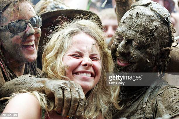 Festivalgoer gets a hug from a man caked in mud on the first day of the Glastonbury Music Festival 2005 at Worthy Farm Pilton on June 24 2005 in...