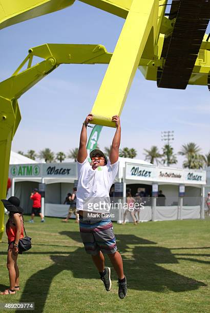 Festivalgoer hangs from the EarthMover art installation by Christian Ristow during day 1 of the 2015 Coachella Valley Music Arts Festival at the...