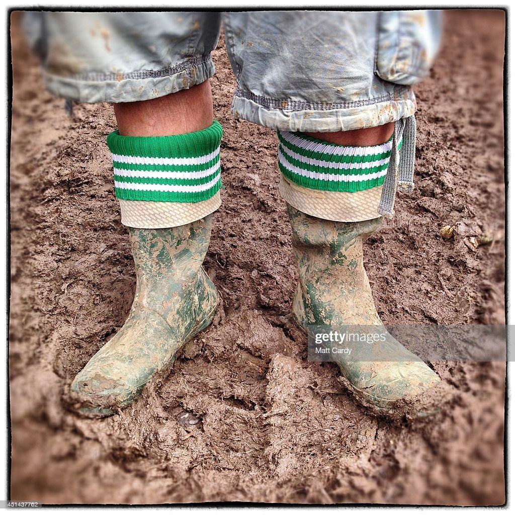 Festival-goer Ian Bowman poses in the mud with his wellies bought at House of Fraser for £80 at the Glastonbury Festival site on June 29, 2014 in Glastonbury, England. Gates opened on Wednesday at the Somerset dairy farm that plays host to one of the largest music festivals in the world. Tickets to the event, which is now in its 44th year, sold out in minutes even before any of the headline acts had been confirmed. The festival, which started in 1970 when several hundred hippies paid £1, now attracts more than 175,000 people