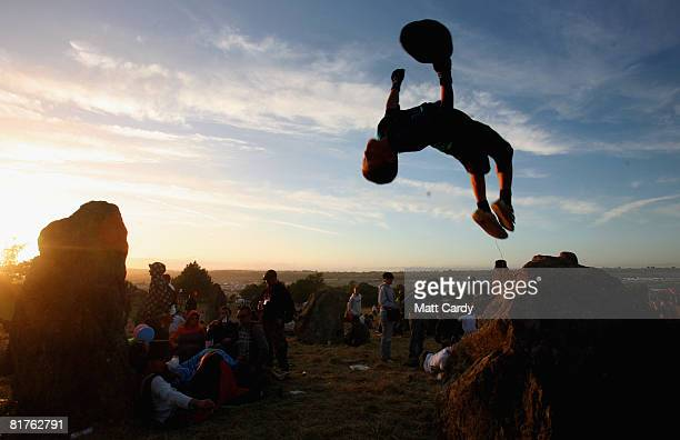A festivalgoer jumps off a stone as people watch the sunset at the stone circle at the Glastonbury Festival at Worthy Farm Pilton on June 29 2008 in...