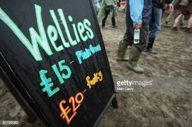 A festivalgoer passes a sign for a stall selling wellies at the Glastonbury Festival on June 27 2008 in Glastonbury Somerset England The threeday...