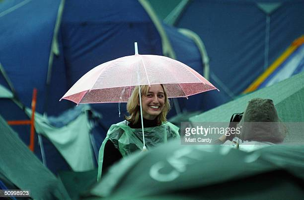 Festivalgoer poses in the rain on the second day of the Glastonbury Festival 2004 at Worthy Farm Pilton on June 26 2004 in Somerset England The...