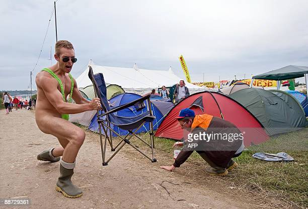 A festivalgoer reatcs as another reveller shows off his mankini on the final evening of the annual Glastonbury festival near Glastonbury Somerset on...