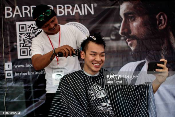 A festivalgoer receives a haircut on day one of the Maho Rasop Festival 2019 on November 16 2019 in Bangkok Thailand