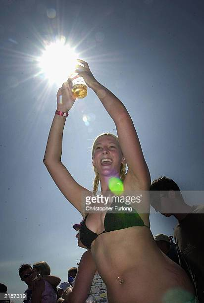 A festivalgoer soaks up the atmosphere and the sunshine during The T In The Park Festival on July 13 2003 at Balado near Kinross in Scotland