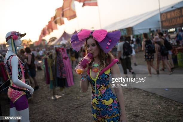 A festivalgoer takes a drink in the West Holts area on the third day of the Glastonbury Festival of Music and Performing Arts on Worthy Farm near the...