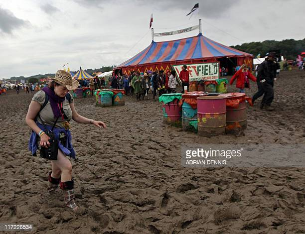 A festivalgoer trudges through the mud at Glastonbury festival near Glastonbury Somerset on June 24 2011 Veteran Irish band U2 are set to rock the...