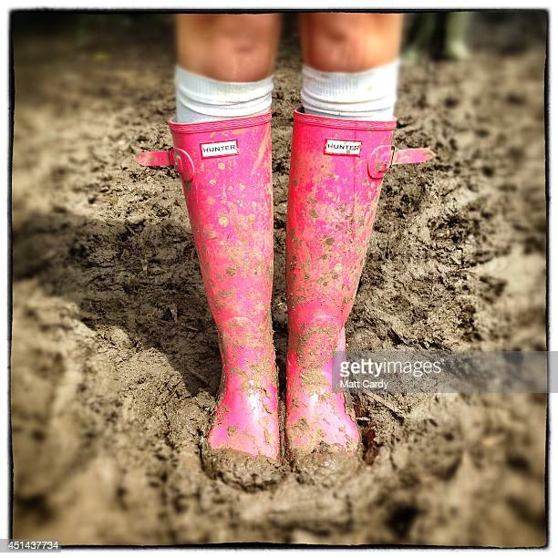 Festivalgoer Vikki Gerard poses in the mud with his wellies bought in a Manchester boutique for £90 at the Glastonbury Festival site on June 29 2014...
