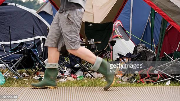 A festivalgoer walks past a deserted tent on the final evening of the annual Glastonbury festival near Glastonbury Somerset on June 28 2009 Running...