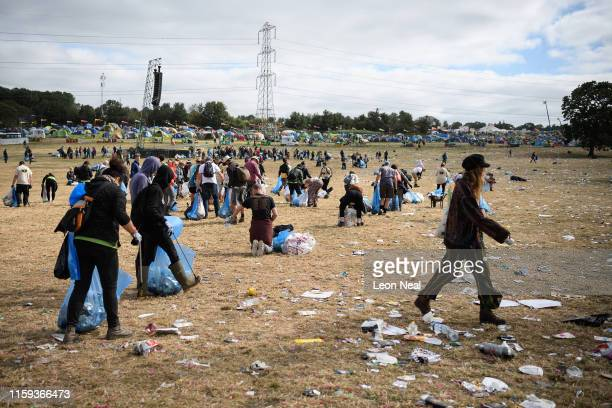 Festival-goer walks through a clean-up crew as it clear litter and debris from the area in front of the Pyramid Stage on the morning after the final...