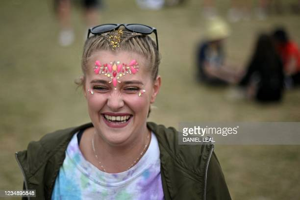 Festival-goer wearing face jewellery smiles at Reading Festival in Reading, west of London, on August 27, 2021. - As coronavirus covid-19 infection...