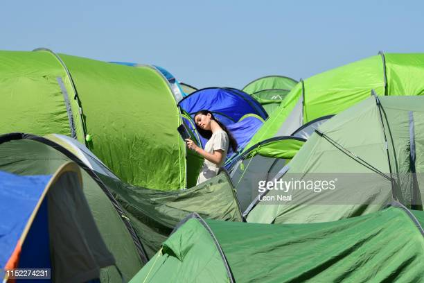 A festivalgoers checks her appearance in a mirror during day two of Glastonbury Festival at Worthy Farm Pilton on June 27 2019 in Glastonbury England...