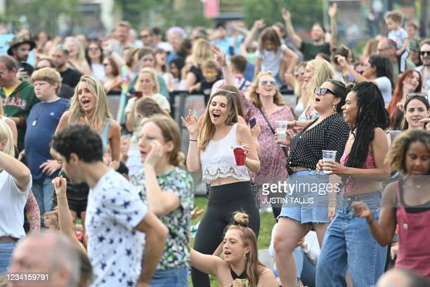 Festival-goers dance as they attend the Kaleidoscope Festival in Alexandra Palace Park in London on July 24, 2021. - The one-day Kaleidoscope...